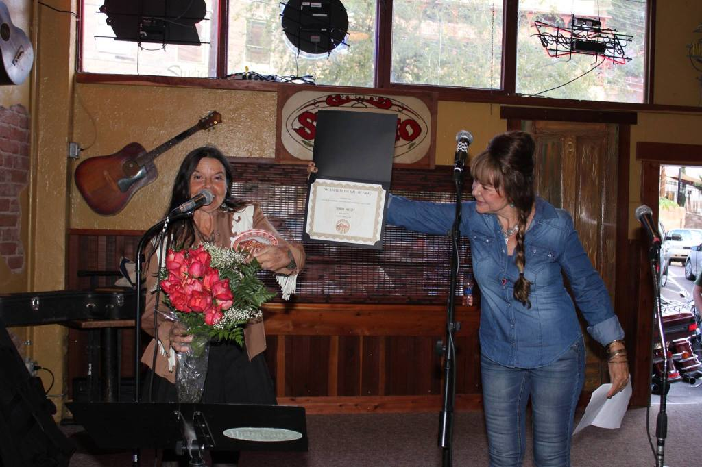 Vanesa Serrano presenting Terry Wolf with her Certificate of Induction to the Bisbee Music Hall of Fame